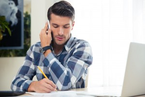 man taking notes while on phone